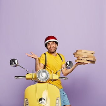 Unaware deliveryman driving yellow scooter while holding pizza boxes