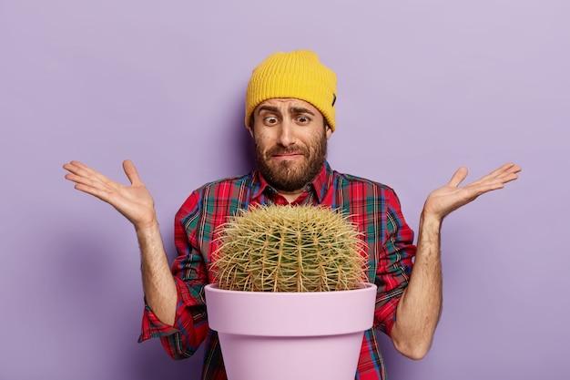 Незнающий садовник позирует с большим кактусом в горшке