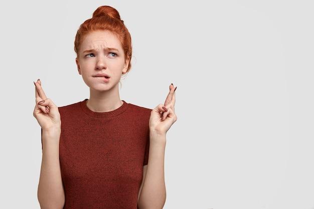 気づいていない生姜のガールフレンドは迷信に見え、成功または幸運を持っているために指を交差させ、唇を噛みます