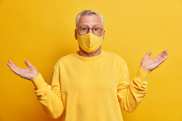 Ignaro uomo dai capelli grigi non sa come ciò che sta accadendo diffonde i palmi delle mani e sta confuso contro il muro giallo vivido indossa una maschera protettiva durante la pandemia di coronavirus