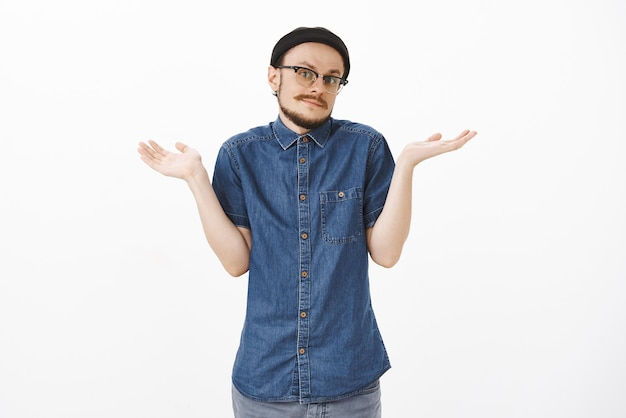 Ничего не подозревающий красивый молодой невежественный парень с бородой и усами в модной хипстерской шапочке и в очках, пожимая плечами, с поднятыми ладонями наклоняет голову и неуверенно поджимает губы