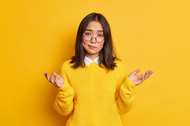 Неосознанная нерешительная азиатка пожимает плечами в невежественном жесте, не может принять решение, носит круглые очки и повседневный джемпер.