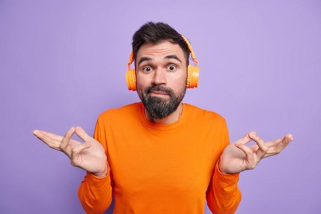 Нерешительный бородатый мужчина разводит руки в сторону, чувствует замешательство, густая борода выглядит невежественно, одет в повседневный оранжевый джемпер, слушает музыку через наушники
