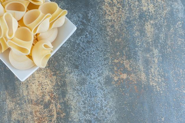 Pasta cruda nella ciotola, sullo sfondo di marmo.