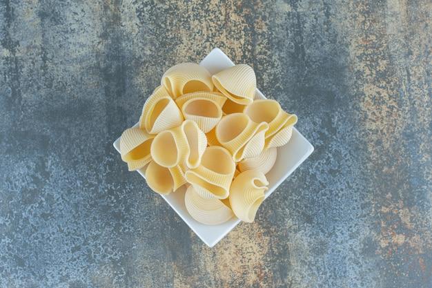 Pasta cruda nella ciotola, sulla superficie di marmo.