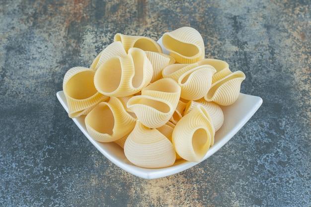 Невыпеченные макароны в миске на мраморной поверхности.