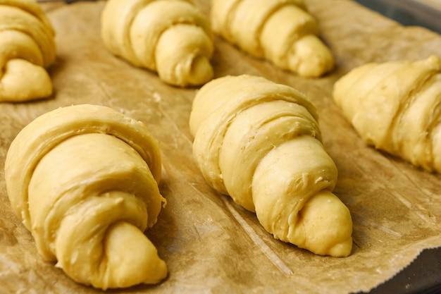 Сырые круассаны на черном подносе с бумагой для выпечки. процесс приготовления десерта из дрожжевого теста. концепция традиционного французского или итальянского теста на дому.