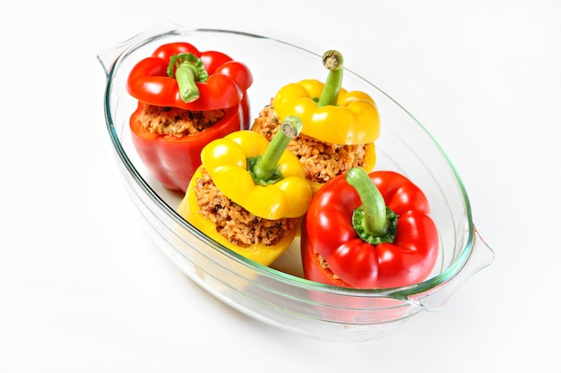 An unbaked yellow and red stuffed peppers served in a heatproof glass