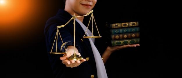 人間の手にある不均衡なスケールの不公正は不公平を意味し、法律書を後回しにします。人々は正義と公正を望んでいます。黒の背景のコピースペース