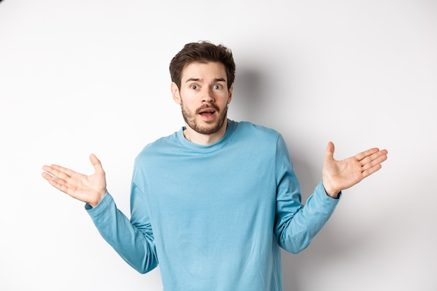 Unbelievable. amazed young man looking with disbelief, spread hands sideways and staring impressed, standing over white background.