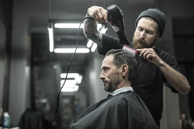 あごひげとタトゥーのある信じられないほどの理髪店が、理髪店の黒いカッティングヘアケープでクライアントの髪を乾かしています