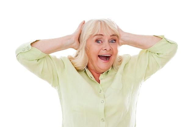 믿을 수 없는! 흰색 배경에 격리된 채 머리를 잡고 웃고 있는 행복한 노년 여성