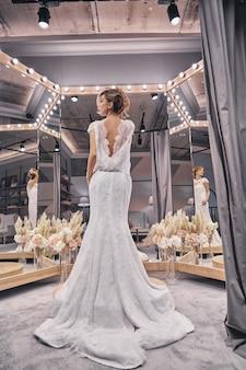 믿을 수 없을만큼 아름답습니다. 신부 가게에서 거울 앞에 서 있는 동안 놀라운 웨딩 드레스를 입고 매력적인 젊은 여성의 전체 길이 후면보기
