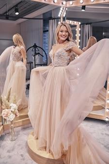 믿을 수 없을만큼 행복합니다. 웨딩 드레스를 입고 신부 가게의 거울 앞에 서서 웃고 있는 매력적인 젊은 여성의 전체 길이
