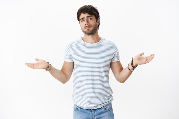 Беззаботный и беззаботный мачо сексуальный парень в полосатой футболке с масками и голубыми глазами раскинул руки в стороны в жесте «мне все равно», будучи крутым и холодным, теперь дает признак интереса