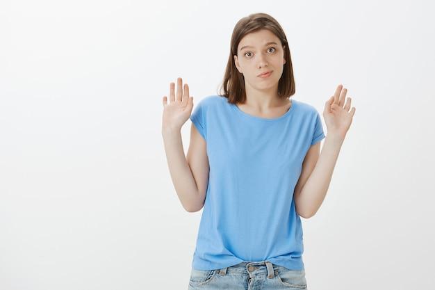Беспокойная скептическая женщина поднимает руки вверх и смотрит в сторону, не желая участвовать, будучи не вовлеченной