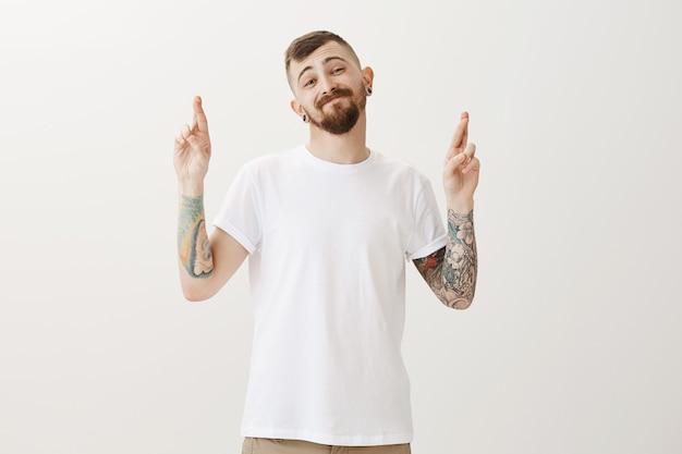 Un ragazzo elegante e disinvolto con tatuaggi incrocia le dita, buona fortuna e sorride spensierato