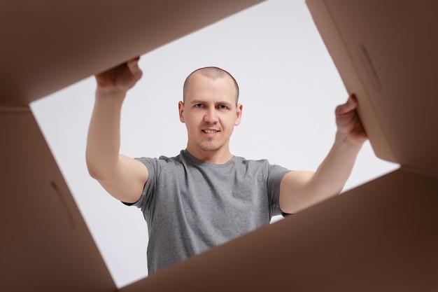 ビュー内の開箱。配達された箱を小包で開梱する若い男