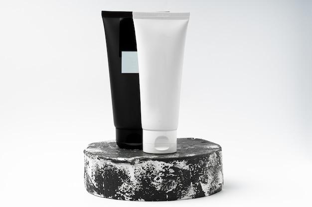 Черно-белые тубы косметического продукта других производителей на черно-белом пьедестале или подиуме на белом фоне. лосьон или крем для ухода за кожей на модной витрине. горизонтальное фото