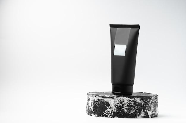 Черная туба косметического продукта других производителей на черно-белом постаменте или подиуме на белом фоне. лосьон или крем по уходу за кожей на модной витрине. горизонтальное фото. место для текста.