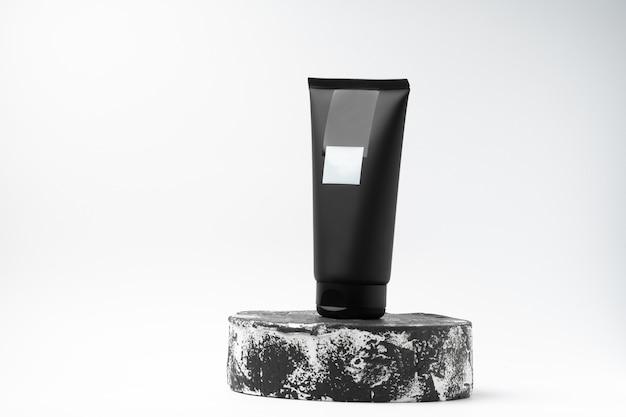 Черная туба косметического продукта других производителей на черно-белом постаменте или подиуме на белом фоне. лосьон или крем по уходу за кожей на модной витрине. горизонтальное фото.