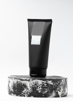 Черная туба косметического продукта других производителей на черно-белом постаменте или подиуме на белом фоне. лосьон или крем для ухода за кожей на модной витрине. вертикальное фото