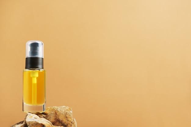 Бутылка с дозатором на камнях других производителей. прозрачный контейнер с маслом для лосьона для лица на естественном фоне. скопируйте пространство с правой стороны. косметология и понятие красоты.