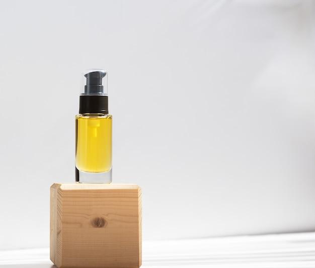 Бутылка с дозатором на деревянной подставке других производителей. прозрачная стеклянная емкость с маслом для тела. ремонт, увлажнение поврежденных волос. косметология и понятие красоты. скопируйте пространство. изолированные на белом.