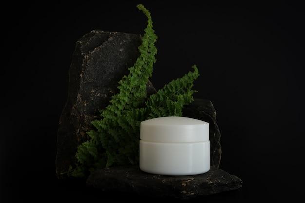 Упаковка натурального косметического крема других производителей на каменном подиуме. презентация крема на черном фоне. макет. актуальная концепция в натуральных материалах. натуральная косметика, уход за кожей.