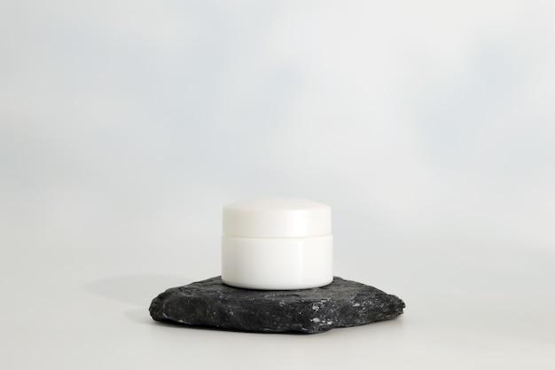 Упаковка натурального косметического крема других производителей на каменном подиуме. презентация сливок на белом фоне. макет. актуальная концепция в натуральных материалах. натуральная косметика, уход за кожей.