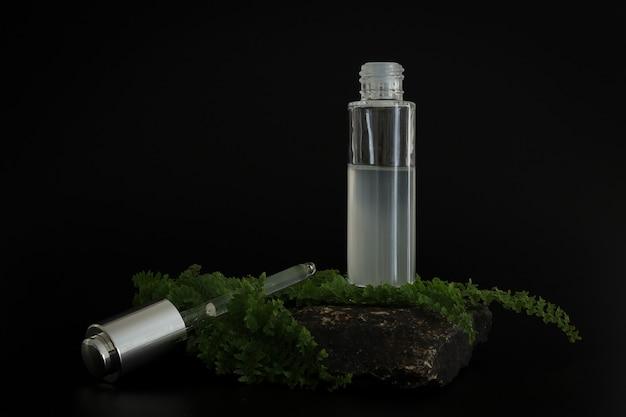 Упаковка натуральной косметической сыворотки других производителей на каменном подиуме. презентация сыворотки на черном фоне. макет. актуальная концепция в натуральных материалах. натуральная косметика, уход за кожей.