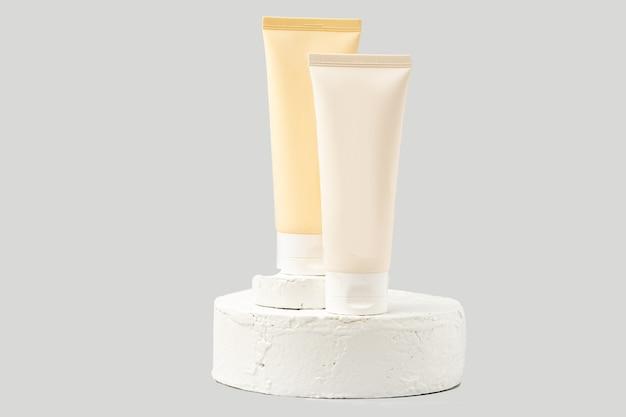 Туба косметического продукта других производителей на белом постаменте или подиуме на белом фоне. лосьон или крем для ухода за кожей на модной витрине. горизонтальное фото