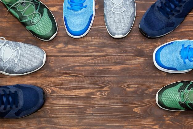Дисплей магазина взгляд сверху unbranded современных новых стильных кроссовок идущих ботинок для людей на деревянной текстуре предпосылки с космосом экземпляра.