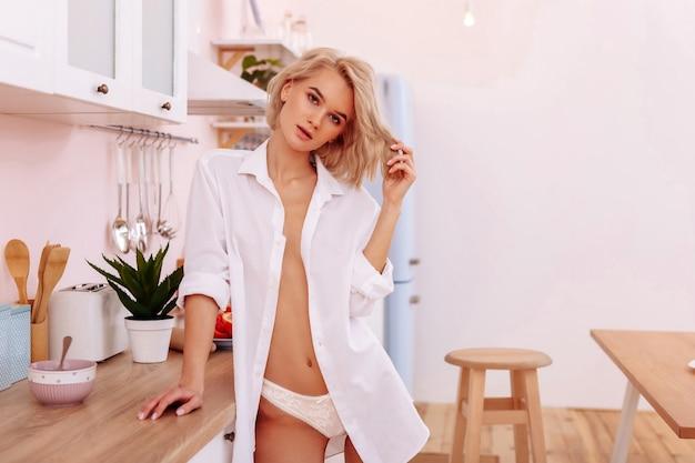 단추가 없는 셔츠. 단추가 없는 셔츠에 그녀의 놀라운 몸과 복근을 보여주는 섹시한 슬림 여자 친구