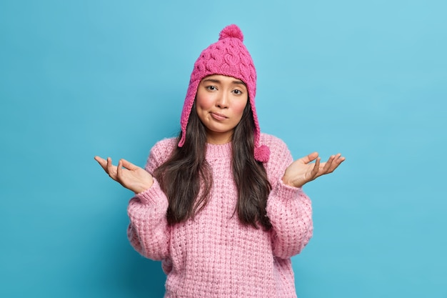 Uncertain beautiful asian woman has dark hair spreads palms sideways stands clueless and confused dressed in winter sweater hat looks with questioned expression isolated over blue studio wall