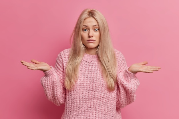 Uncertain blonde woman spreads palms and stands doubtful indoor cannot make choice between two options wears knitted warm sweater