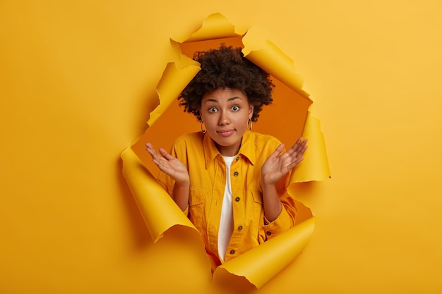Uncertain cute woman with afro hairstyle spreads palms, has confused clueless expression makes decision, shrugs shoulders has no idea poses in yellow paper hole background.