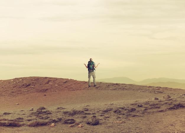 不確かな探検家の男が砂漠で迷子になっている