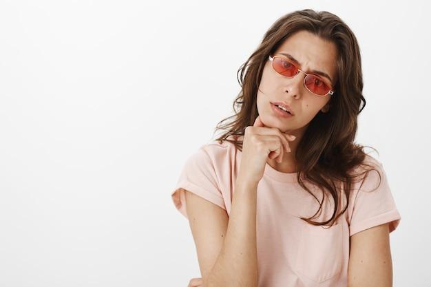 Неуверенная девушка в солнцезащитных очках позирует у белой стены