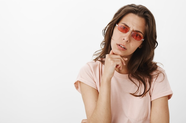 Uncertain girl with sunglasses posing against the white wall