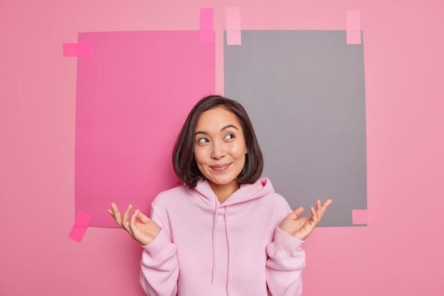 Неуверенная неуверенная азиатская женщина раздвигает ладони, чувствует себя неосведомленной, думает о выборе, понятия не имеет, будучи невежественной стоит, сомневается, носит повседневную толстовку с капюшоном, позирует на фоне пустой пустой стены