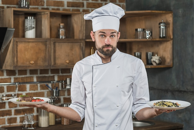 Uncertain male chef holding two different dish on his hand