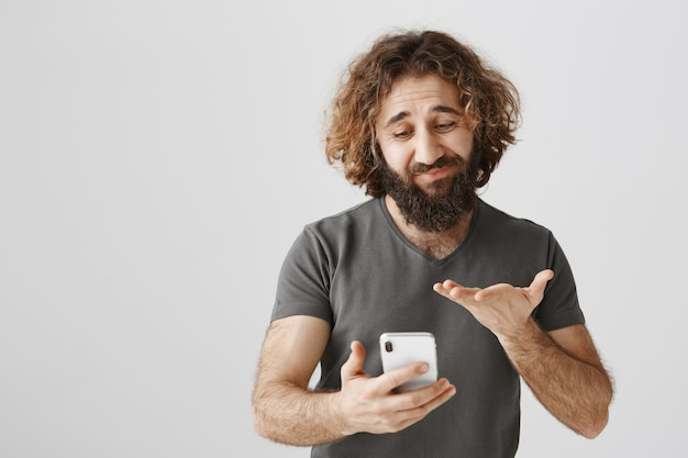 Uncertain middle-eastern man looking at mobile phone indecisive, feeling hesitant