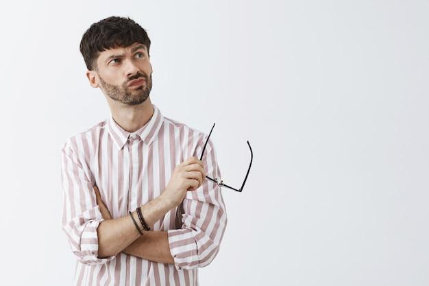 眼鏡をかけて白い壁にポーズをとる不確かなスタイリッシュなひげを生やした男