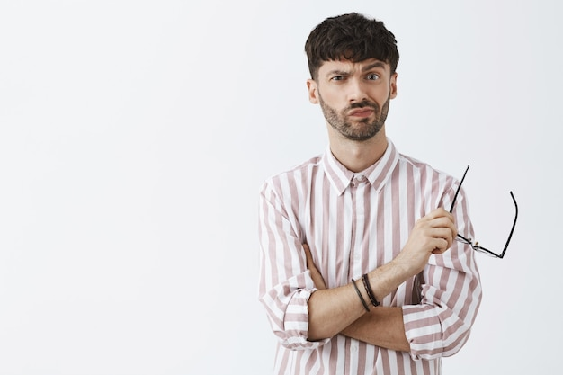 Uncertain stylish bearded guy posing against the white wall with glasses