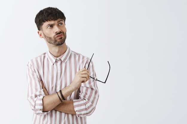 Ragazzo barbuto elegante incerto in posa contro il muro bianco con gli occhiali