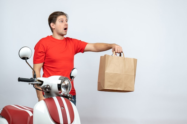 白い壁に紙箱を与えるスクーターの近くに立っている赤い制服を着た不確かな不確かな配達人