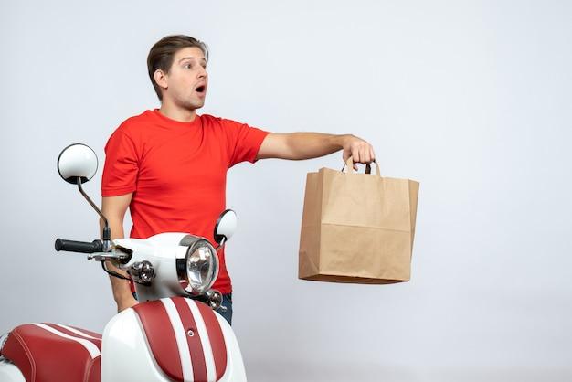 Incerto fattorino incerto in uniforme rossa in piedi vicino a scooter dando scatola di carta sul muro bianco