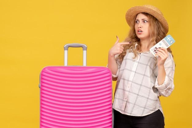 Неуверенная и неуверенная молодая дама в шляпе показывает билет и стоит рядом со своей розовой сумкой, указывая на себя