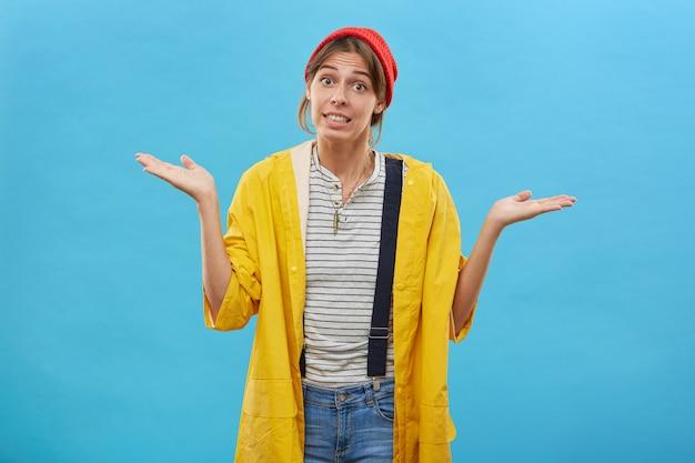 決断を下す勇気がない肩をすくめ、脇を上げた手で立っている不確実な女性。雨の日の屋外で散歩をするつもりの黄色のレインコートを着ている若い主婦